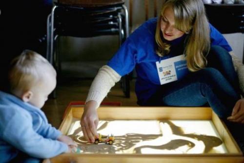 Caritas Mitarbeiterin spielt mit Flüchtlingskind