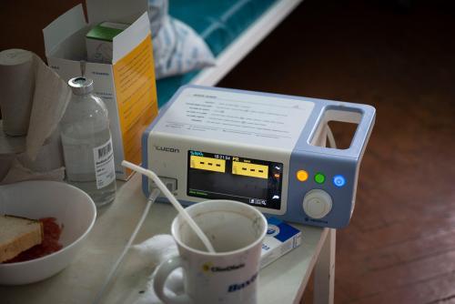 Ein Tischchen neben dem Krankenhausbett im Zimmer für Intensivbehandlung. In der Mitte ein gerade angeschlossenes Pulsoximeter